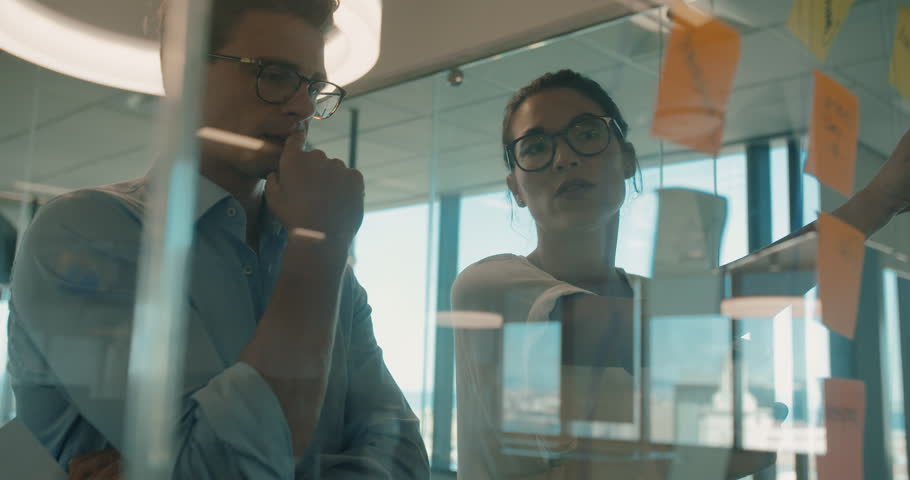 Business woman presenting her ideas to male colleague on sticky notes over glass wall. Business man and woman brainstorming in modern office.