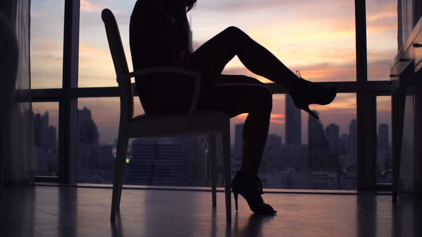 Silhouette of woman taking off high heels sitting on chair, super slow motion 240fps