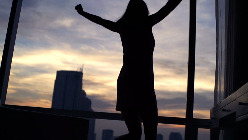 Silhouette of happy woman jumping off armchair by window, super slow motion 240fps  #24555497