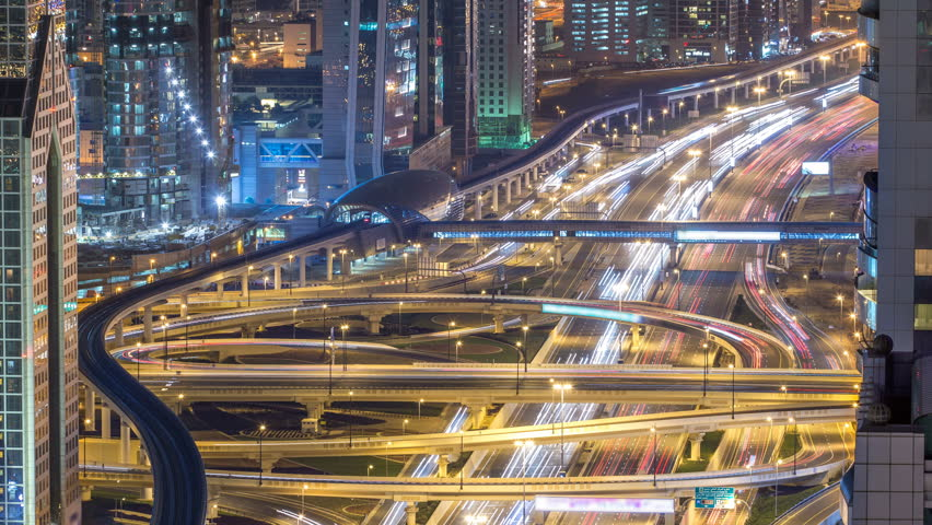 Aerial top view of highway junction with traffic timelapse in Dubai, UAE, at night. Famous Sheikh Zayed road in Dubai downtown. Transportation and driving concept view from rooftop.