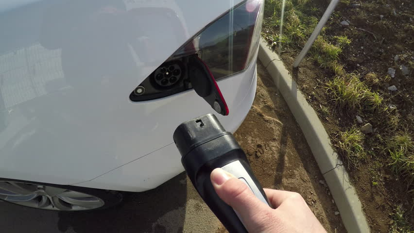 KOZINA, SLOVENIA - FEBRUARY 4, 2017: Environmentally friendly luxury Tesla Model S electric car charging battery cells at supercharging station. Unrecognizable person plugging in the cable to charger