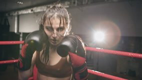 Fighter woman fist close up - boxer strikes into the side of the camcorder. Spectator video boxing. Strong aggressive young girl woman boxing in the ring as a symbol of feminism and successful women