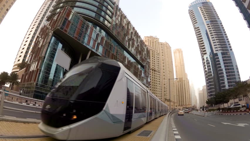 Modern tram rides on rails among the skyscrapers in Dubai, UAE Royalty-Free Stock Footage #24580643