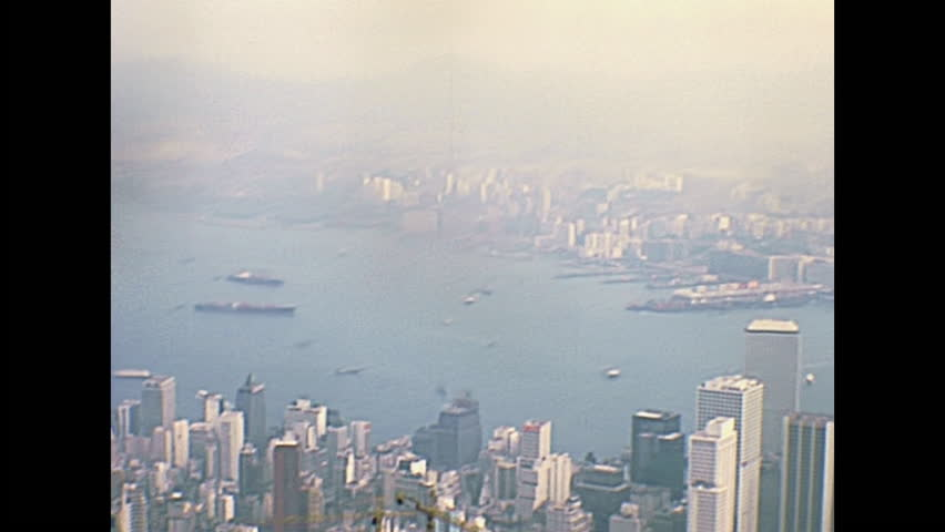 Aerial view of Victoria Harbour skyline from overlook on top of the Peak Tower, icon building in Hong Kong, China. Historic restored footage on 1980 with boats and few buildings.