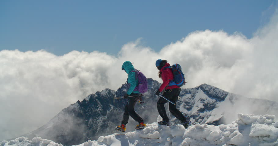 Two female mountaineers descending a rubble field of avalanche debris roped together for safety as a storm front approaches over the high altitude mountains in the distance.