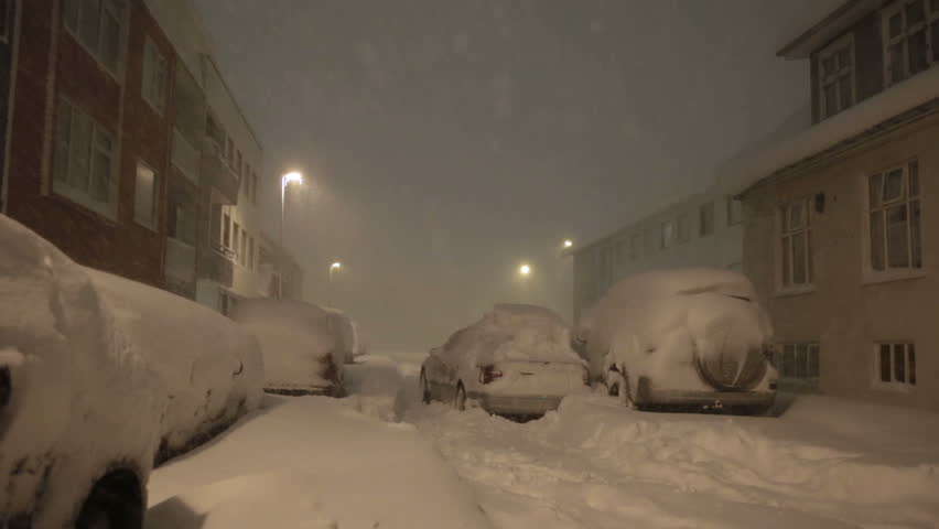 High winds snow blizzard abandoned car in residential street Reykjavik Iceland