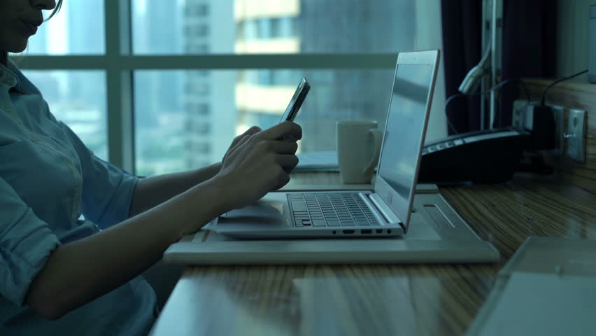 Businesswoman with smartphone and laptop sitting by desk in office  | Shutterstock HD Video #24596705