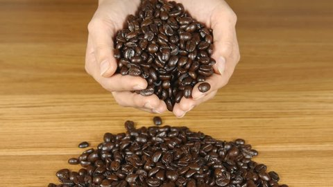 Slow motion of Woman hands holding coffee beans - Inside close up of woman hands holding coffee beans on the table