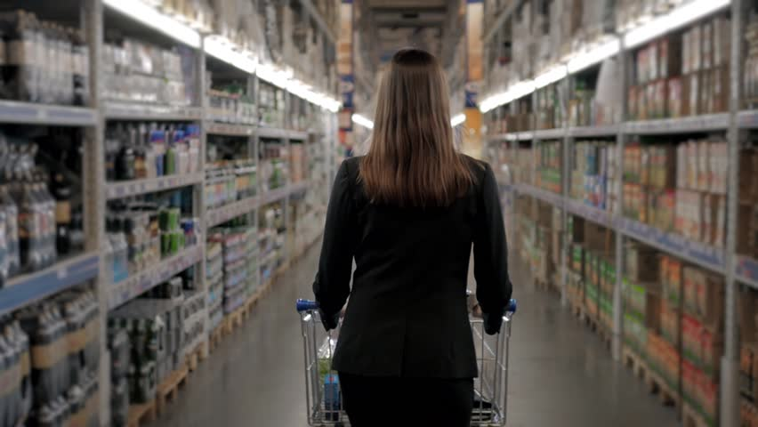 Woman shopping at the supermarket, follow shot from back of young woman with trolley in shopping center, alcohol store. | Shutterstock HD Video #24601613
