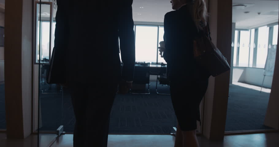 Businessman and businesswoman entering a conference room for business meeting. Business people meet up with other colleagues and shake hands.