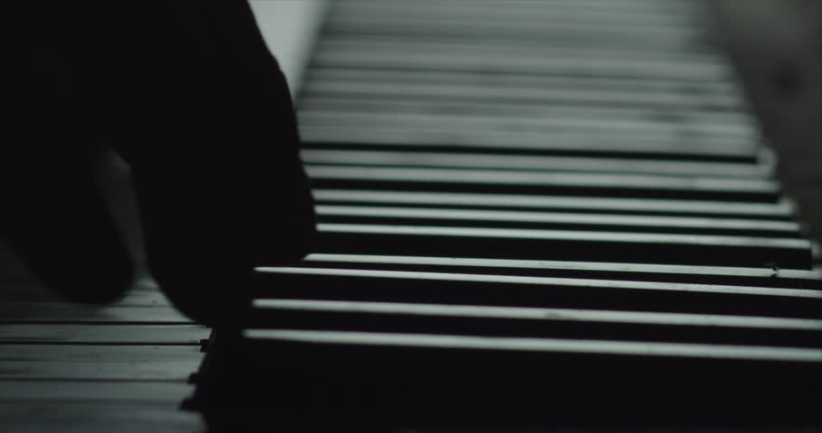 Fingers close up on piano keyboard black and white keys slow motion