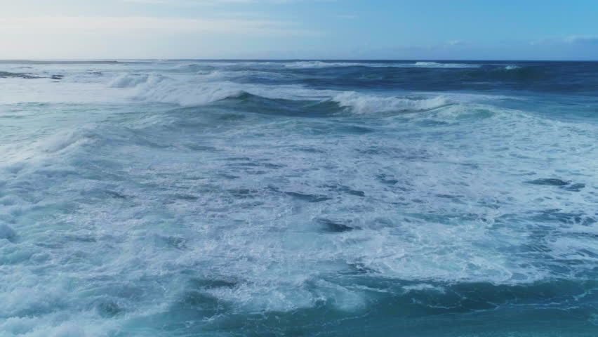 Aerial slow motion of beautiful sea waves. As the waves moves they create texture from white sea foam. Drone footage of seascape against sky.