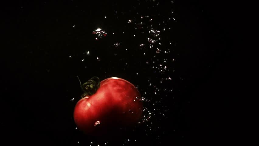 Fresh tomatoe splashes water in aquarium on black background | Shutterstock HD Video #24629381