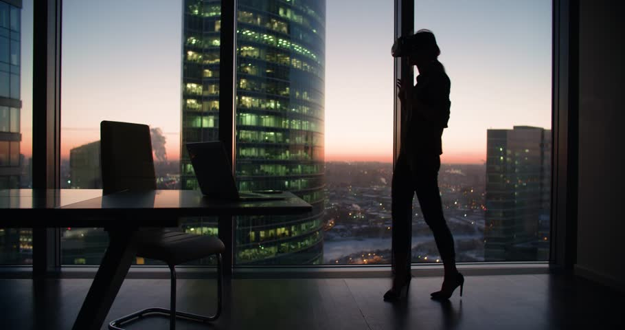 silhouette Technology VR-businessman young girl wearing virtual reality technology VR Glasses to work in modern office in a skyscraper. the creation of the presentation