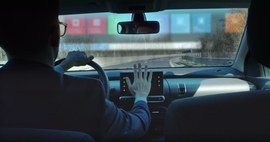 A businessman riding in a futuristic car and following a conference of economics and finance while driving. The call appears in augmented reality with projection of holograms.
