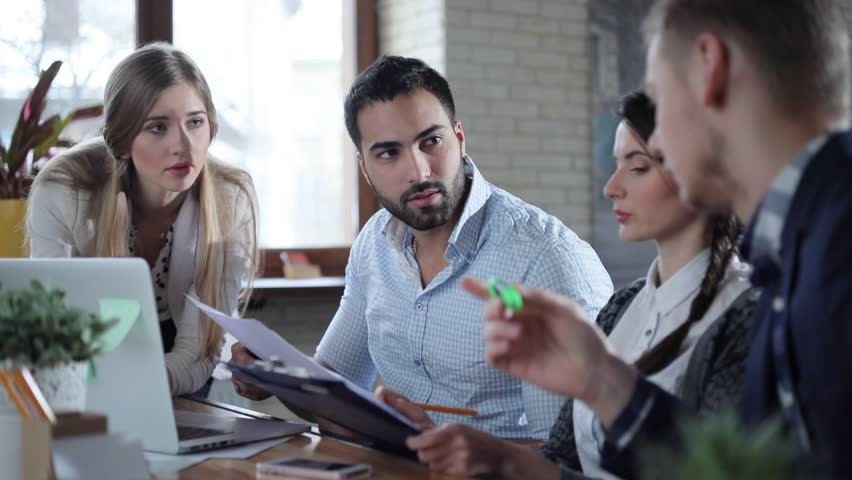 Four young multicultural start-uppers brainstorming at the office and using laptop and some presentations. | Shutterstock HD Video #24636530