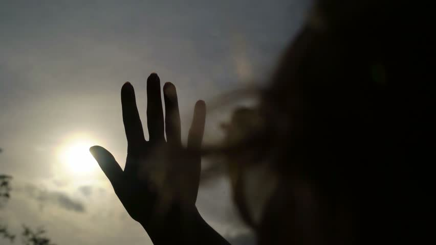 Woman catching the sun by hand silhouette | Shutterstock HD Video #24643028
