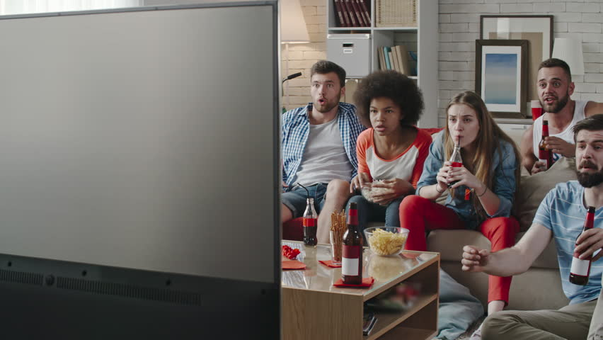 Tracking shot of young friends sitting on sofa and watching sport match on TV. They throwing arms up in excitement and yelling while celebrating goal   Shutterstock HD Video #24648368