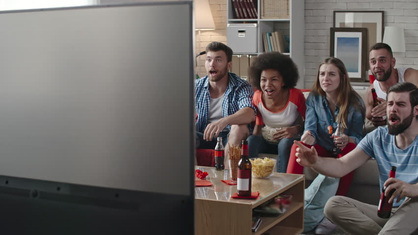 Group of young excited sport fans watching match on TV at home. They drinking beer and soda, eating popcorn and snacks and yelling along with team but getting disappointed   Shutterstock HD Video #24648389
