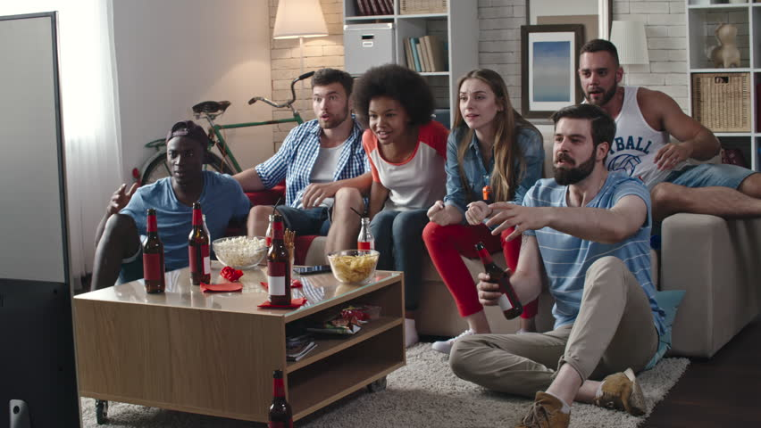 Zoom in of multi-ethnic group of friends celebrating victory of their team. They yelling, clapping hands and whistling while sitting in living room and watching TV match   Shutterstock HD Video #24648476