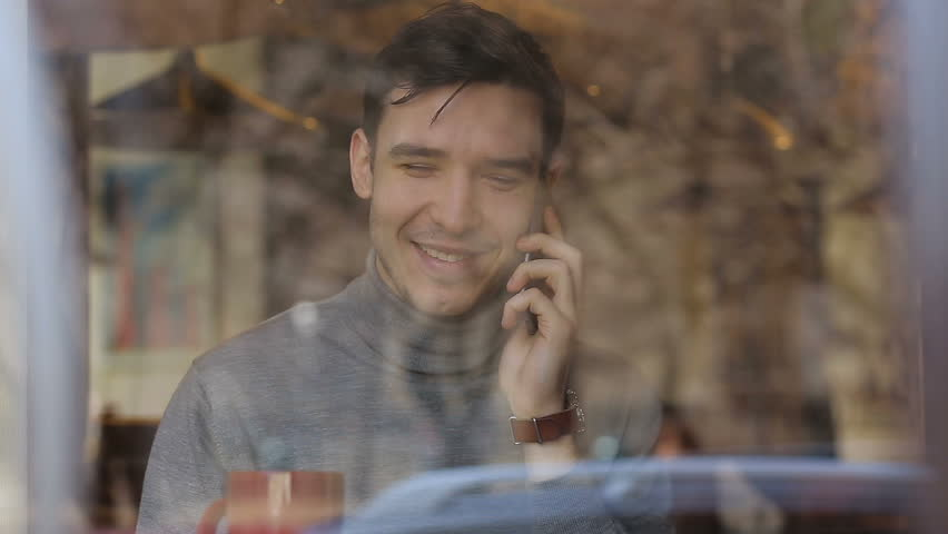 Businessman texting and talking on cellphone in cafe. Shot through window | Shutterstock HD Video #24650750