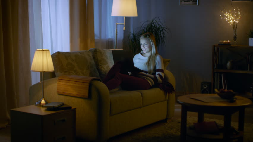 In the Evening Beautiful Young Woman Lies on the Couch with a Laptop on Her Knees. She Types and has Fun. Room Looks Warm and Cozy.  Shot on RED EPIC-W 8K Helium Cinema Camera. | Shutterstock HD Video #24653825