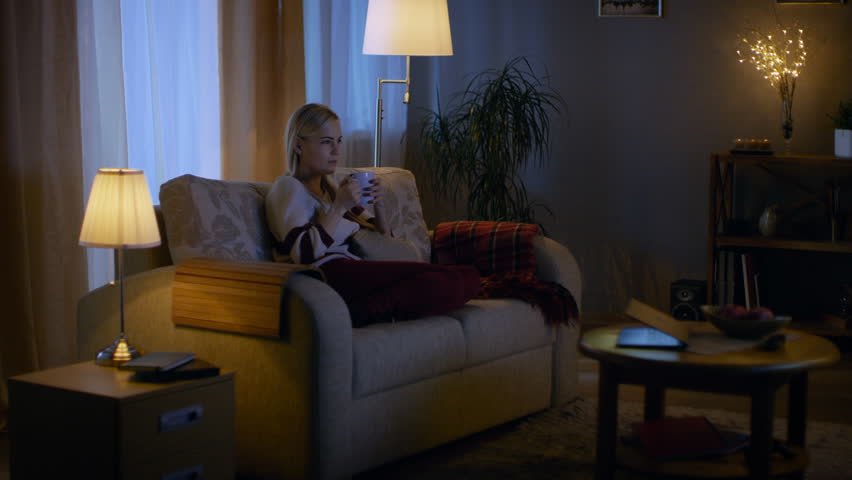 Beautiful Woman Sits on a Couch in Her Cozy Living Room. She Watches TV and Drinks Hot Drink.  Shot on RED EPIC-W 8K Helium Cinema Camera. | Shutterstock HD Video #24653882