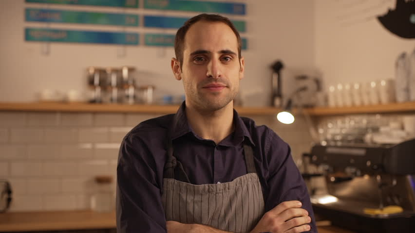 Male Caucasian barista wearing apron standing with folded hands and lightly smiling in slowmotion   Shutterstock HD Video #24661445