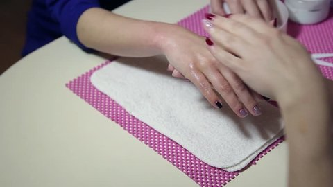 Woman hands in a nail salon receiving a hand massage by a beautician