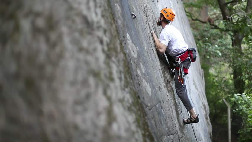 Rock climbing man, climbing with hands, legs and feet on vertical straight wall, very difficult movement. Slow motion 120 fps. Extreme risk outdoor sport. Patagonia Argentina. Trees on the background