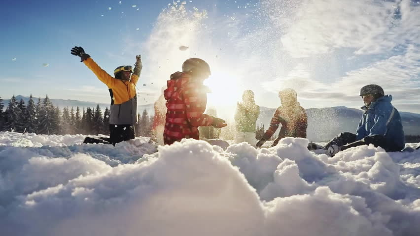 Happy group of skiers having fun sitting in snowdrift with snowboards and tossing snow | Shutterstock HD Video #24686375