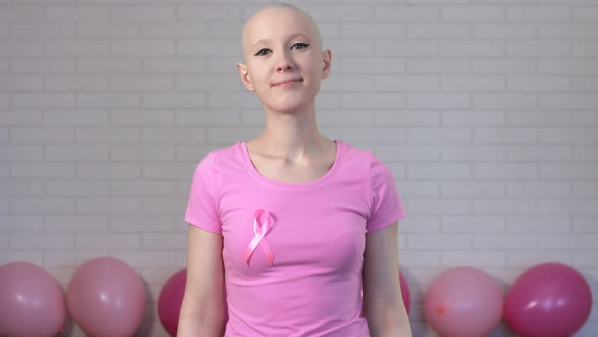 Strong and happy breast cancer survivior woman showing biceps - breast cancer awareness concept