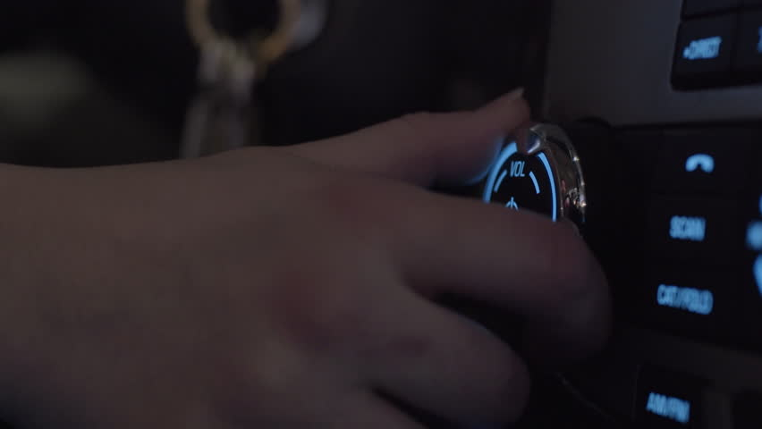 Closeup Of Young Woman's Hand As She Turns Up The Volume In Her Car At Night