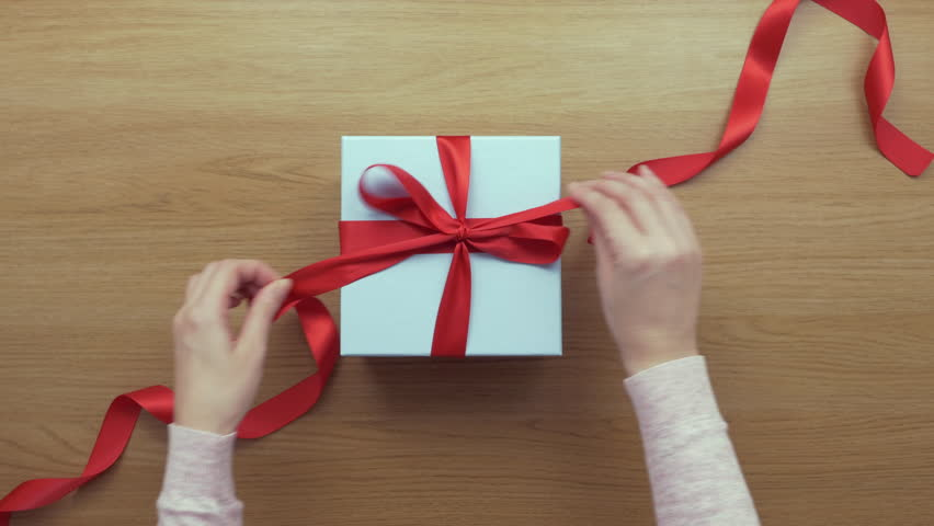 Aerial footage of woman opening red ribbon on gift box. Lockdown shot of female unpacking present on wooden table. Personal perspective of lady unpacking empty box.