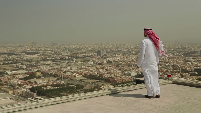 Wide shot of a Saudi Arabian man in local dress standing on a roof looking out across the city of Jeddah, In Saudi Arabia in the Middle East on a windy day.