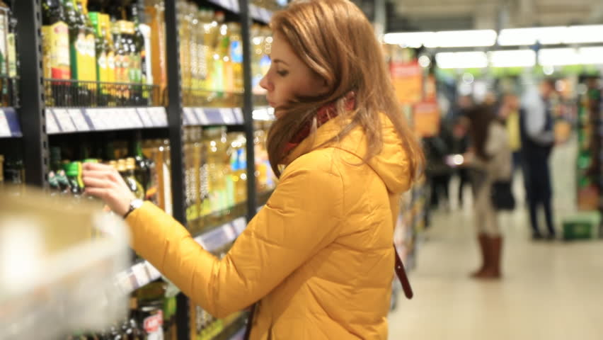 Young redhead woman picking an olive oil bottle from the shelves of a supermarket and reading the label | Shutterstock HD Video #24719846