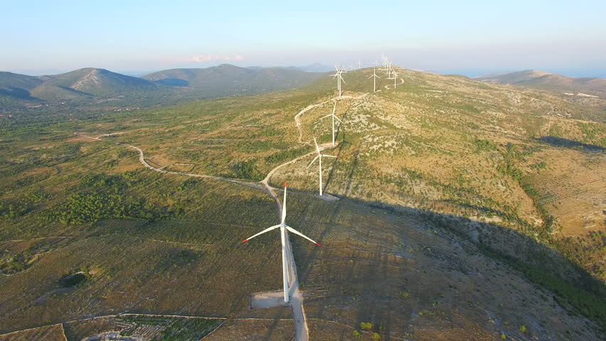 Aerial view of group of white windmills on a hill path #24726425