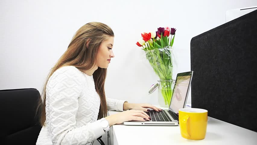 Young beautiful pin-up girl sitting behind a desk and working at a computer. Flowers, yellow cup, office.