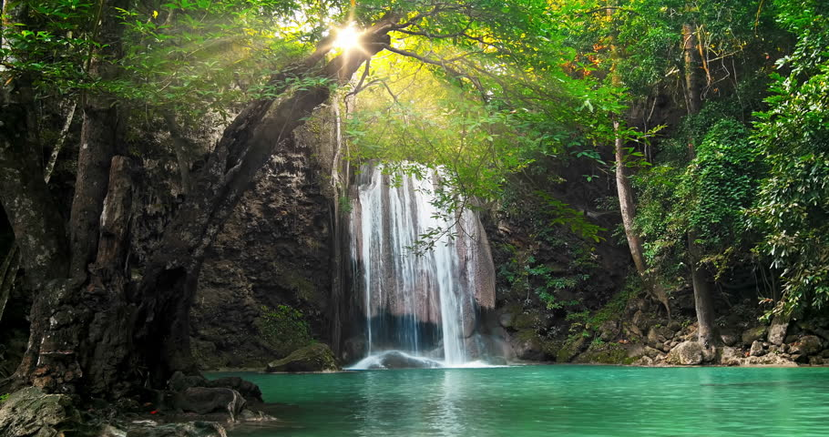 Majestic waterfall and beautiful tropical nature with sun light shining through tree branches in Erawan national park, Kanchanaburi, Thailand | Shutterstock HD Video #24743147
