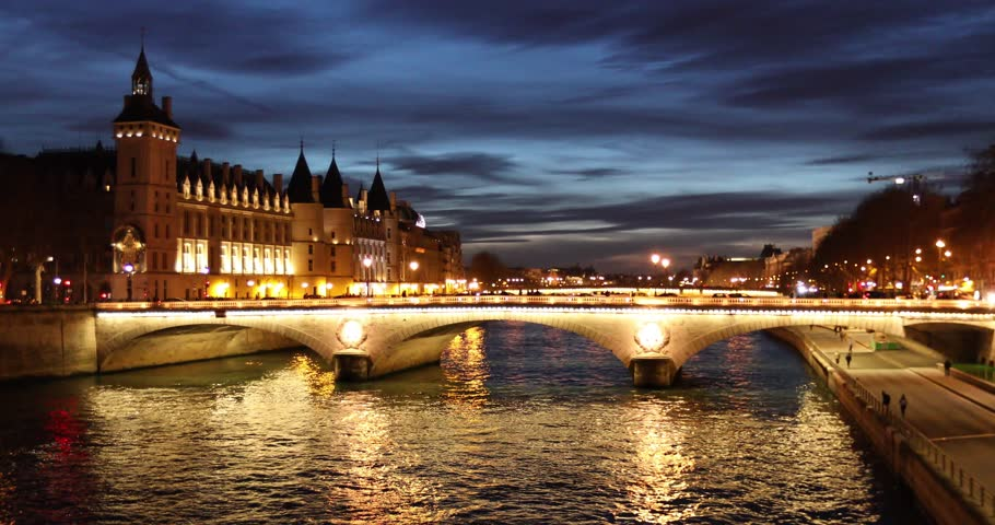 Parisian cityscape with traditional architecture, bridge, and the Seine river at night during blue hour with illuminated streets
