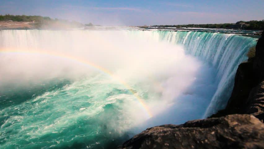 Beautiful Horseshoe Waterfall on Sunny Day with Mist Producing a Rainbow in Niagara Falls Ontario Canada