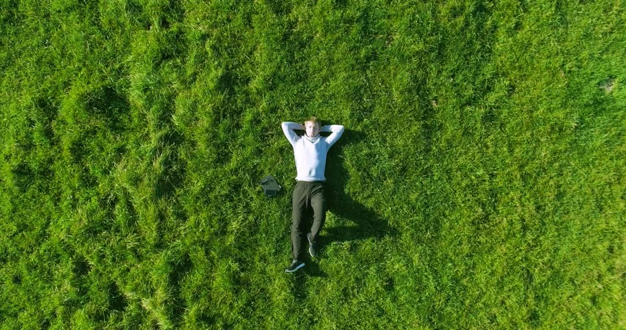 Aerial UHD 4K view. Vertical motion flight over businessman lying on fresh green meadow at sunny summer morning. Top view on handsome relaxing man.   Shutterstock HD Video #24765374