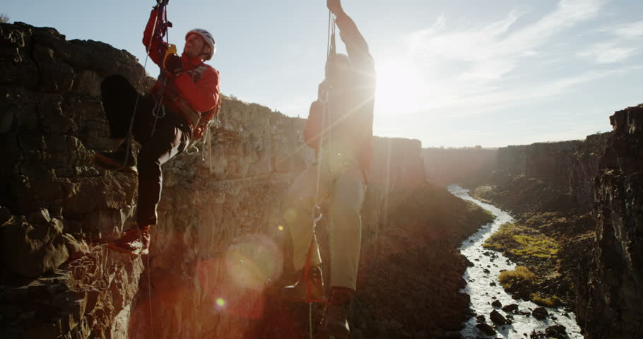 Two men climbing up ropes over canyon with river and sun in background
