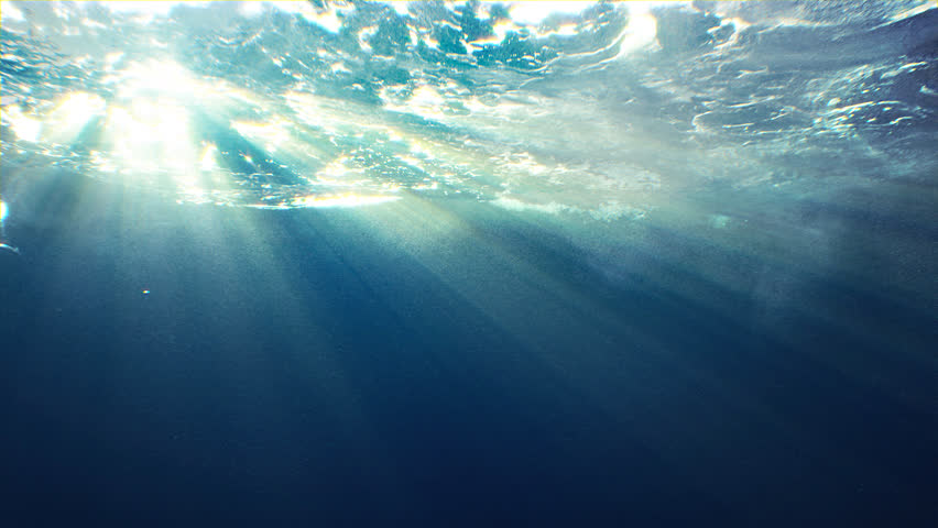 Beautiful underwater sea scene view with natural light rays, shining through the water's glittering and moving surface, caustics, bubbles, and foam, perfect for background and digital composition