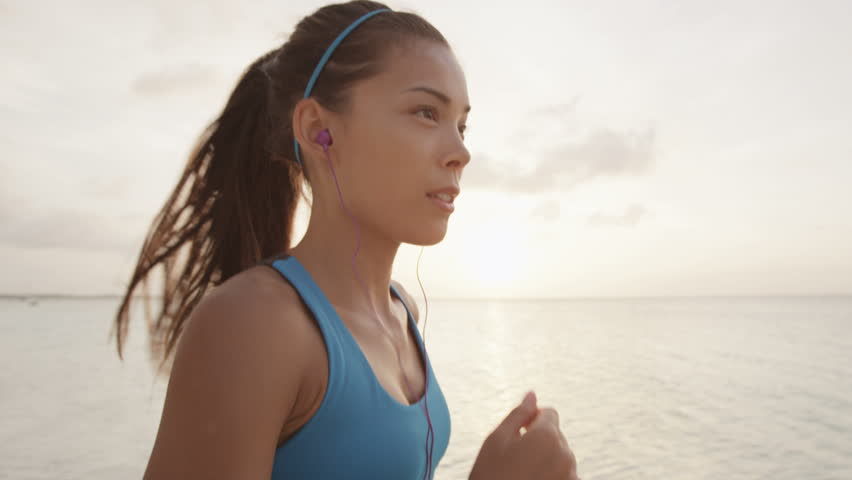 Runner woman getting ready to run and starts running on beach at sunset wearing earphones listening to music. STEADICAM SLOW MOTION, RED EPIC.