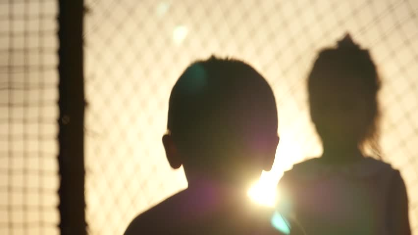 Silhouettes of young children running around the trampoline on a background of sea sunset backlit