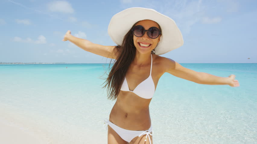 Bikini beach woman happy smiling playful cheerful having fun dancing around. Bikini girl wearing sunglasses excited and joyful. Beautiful sexy mixed race woman having fun on summer travel vacation. #24787574