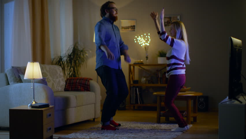 Happy Couple Dances in Their Living Room with TV Turned On. Their House is Cozy and Warm. It's Evening.  Shot on RED EPIC-W 8K Helium Cinema Camera. #24787604