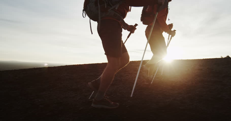 Two men hiking in silhouette past rising sun slow motion