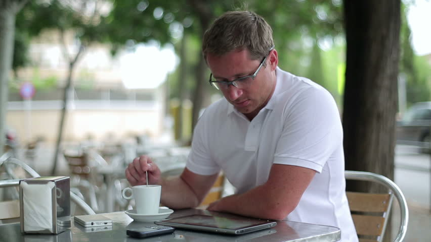 Young man working on tablet computer in cafe, outdoor  | Shutterstock HD Video #2480300
